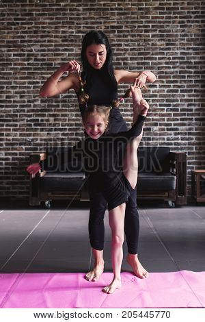 Young mother holding pig-tails of her smiling daughter doing standing split at home.