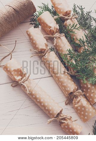 Wrapping gifts background. Handmade christmas present or garland candies from maroon paper with craft rope. Closeup of white wooden table, winter holidays decorations and ornaments, copy space