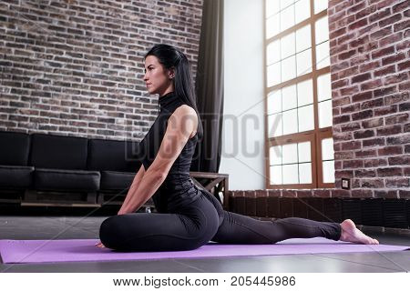 Side view of pretty brunette wearing sports outfit sitting in king pigeon pose, Eka Pada Rajakapotasana, practicing yoga at home.