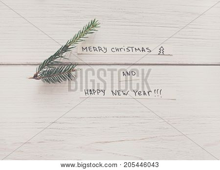 Christmas celebration background. Top view of white wooden table with congrats for xmas and new year on sheet of paper with fir tree branch. Winter holidays concept, copy space