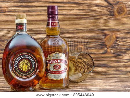 Ternopil Ukraine - August 26 2017: Bottles with Brandy Vecchia Romagna and whisky Chivas Regal . Diferent alcoholic beverages bottles with glasses on a wooden background.