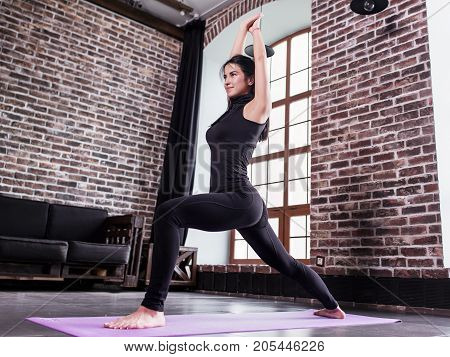 Pretty young female athlete in black sports outfit doing lunge exercise or standing in yoga low warrior pose on mat at home.