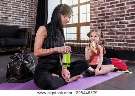 Young Caucasian woman and a happy girl child relaxing after yoga training sitting on mat with legs crossed drinking water, eating banana in sports studio.