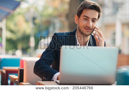Multitasking. Young businessman working on laptop and talking on phone, at the table on colorful cafe terrace. Smiling freelancer, in casual jacket, unbuttoned shirt typing, looking to laptop screen