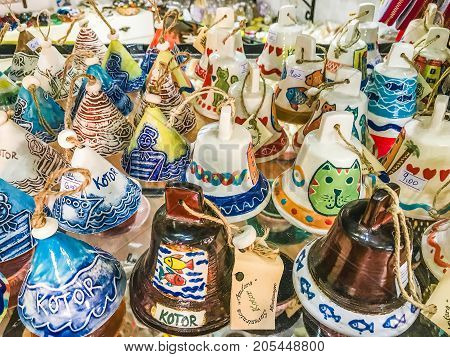 Kotor, Montenegro - August 24, 2017:  Selection of souvenirs from the old town of Kotor, Montenegro. Souvenir trade - various bells with Kotor inscriptions and beautiful drawings.
