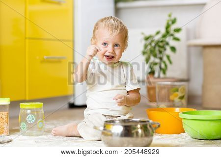 Child little boy playing with kitchenware and foodstuffs in kitchen