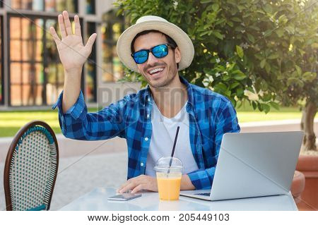 Outdoor Horizontal Closeup Of Optimistic Caucasian Guy Pictured In Street Cafe At Table Wearing Sun