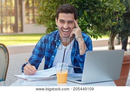 Outdoor Portrait Of Young Positive Caucasian Male Sitting At Café Table Outdoors And Filling In Form