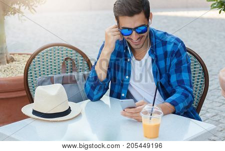 Closeup Picture Of Trendy European Guy In Blue Casual Shirt Smiling Widely While Looking To Screen,