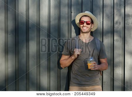 Outdoor Closeup Of Young Trendy European Man Standing Alone With Grey Wooden Fence Behind, Looking A