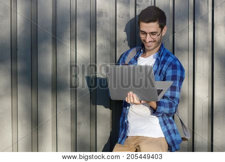 Horizontal Outdoor Image Of Young Handsome European Guy Standing With Backpack Pressed To Gray Woode