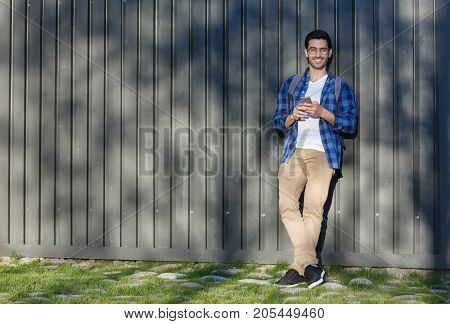Full-height Image Of Young Handsome Caucasian Male Pictured With Grey Wooden Background Behind Holdi