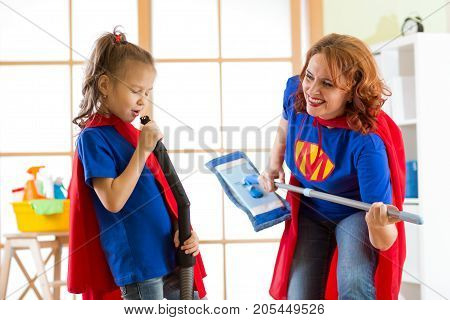 Happy woman and kid daughter is preparing for room cleaning. Mother and her child girl playing together. Family in Superhero costumes.