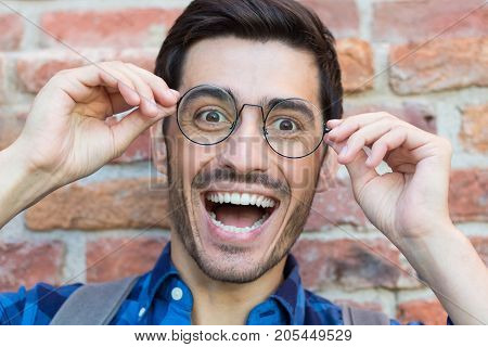 Closeup Image Of Trendy European Male Standing Against Red Brick Background With Round Eyeglasses Sh