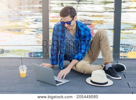 Horizontal Photo Of Young Trendy Caucasian Guy On Wooden Surface Beside Lake Outdoors In Park, Looki