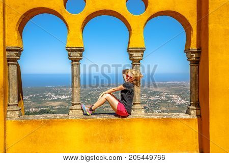 Happy blonde woman sitting on arabic arches of Pena National Palace on top of a hill above Sintra.On background, aerial view of the city.Female traveler visits the biggest tourist attraction of Sintra