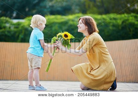Little Boy Offering Bunch Of Sunflowers To His Mom