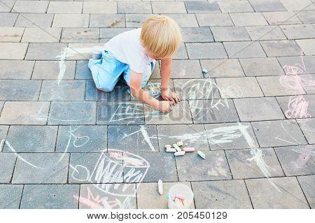 Little Boy Drawing With Chalks On Asphalt