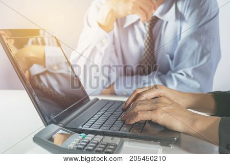Businessman and businesswoman process and using laptop. Businessman and businesswoman working the project on table.