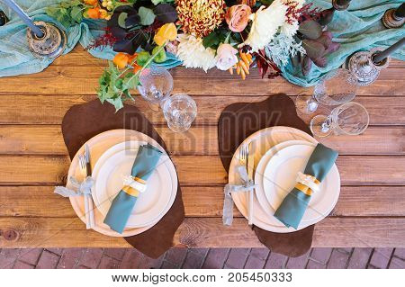 party, engagement, design concept. top veiw of place for newlyweds with magnificent decoration contains delicate flowers, few white plates of different sizes, elegant silverwares and wineglasses