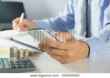 Businessman process with writing and using smart phone. Businessman working the project on table