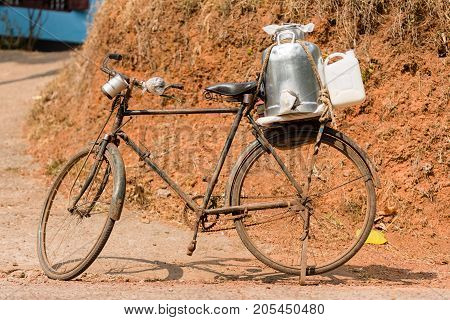 An old and rusty bicycle stands on the road side in Kerala India. It is used by a milkman for deliveries and features a tin gallon and serving cups.
