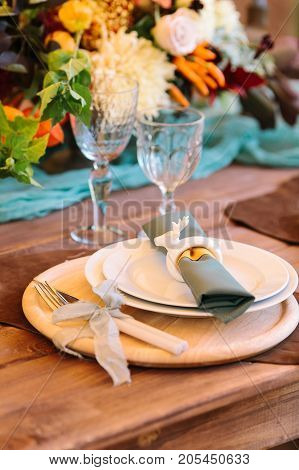 perfection, romance, design concept. tidy fltatware for celebration of wedding with knife and fork strapped of lilar thin ribbon, set of plates, two high aesthetic wineglasses