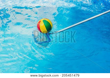 The Toddler Boy Cleans The Pool And Pulls The Ball Out Of The Pool. Pool Cleaner Concept