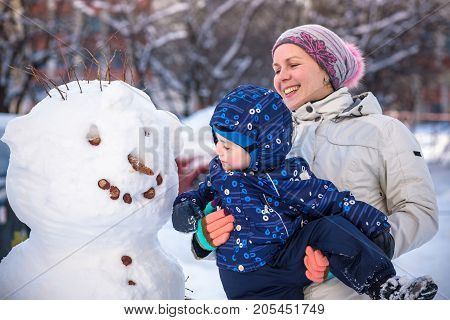 Little toddler boy making snowman outdoors on beautiful winter day with his mother placing carrot like nose happy smiling family