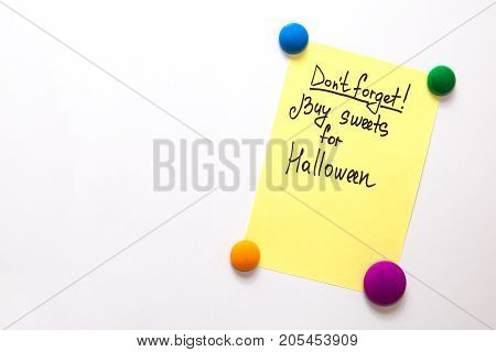 Fridge note with the text: Don't forget! Buy sweets for halloween