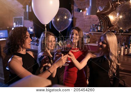 Group of cheerful girls having a party standing clinking glasses together at night club.