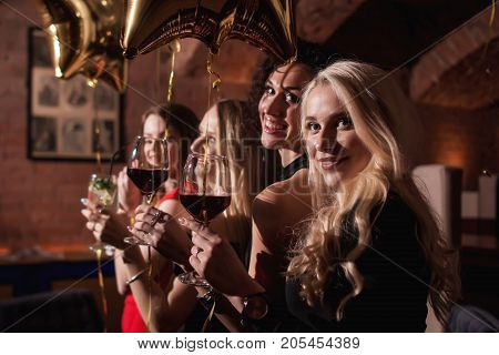 Cheerful young women standing looking back to camera holding glasses of wine celebrating birthday of their girlfriend in restaurant.