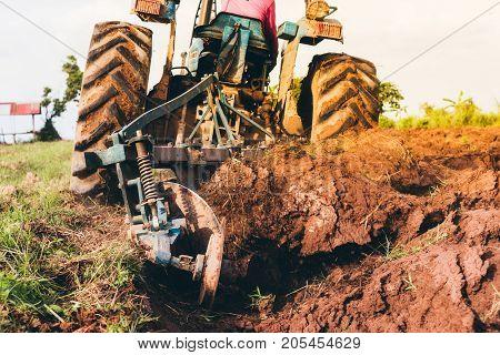 Asia farmer using tiller machine in rice fieldFarmer in tractor preparing farmland.