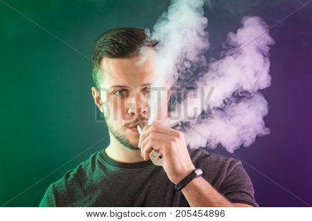 Vaping Man Holding A Mod. A Cloud Of Vapor.