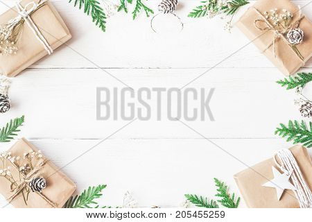 Christmas composition. Frame made of christmas gifts pine cones thuja branches on white wooden background. Flat lay top view copy space