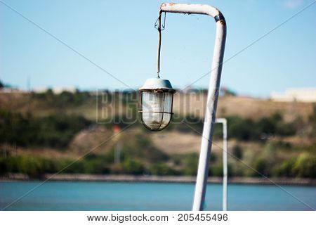 Summer lamp against the blue sky and the river