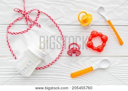 children feeding with breastmilk or infant formula powdered baby milk and toys on wooden white table background top view