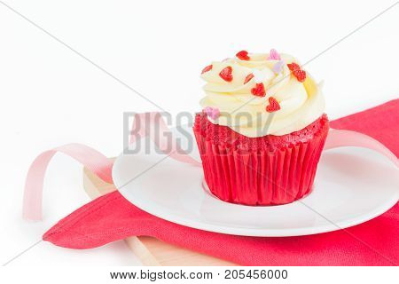 Red Velvet Cup Cake topped with red purple pink heart shaped icing on white background over wood board & red napkin with ribbon for special holiday celebration Valentines day or Christmas occasions