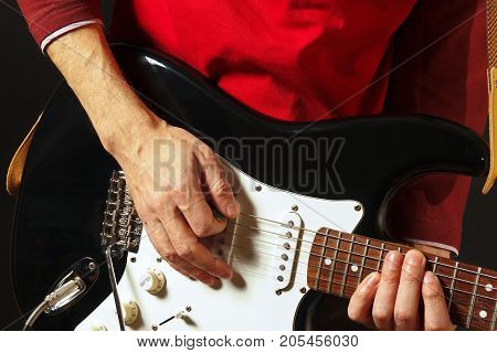 Posing hands of rock guitarist playing the guitar on the black background
