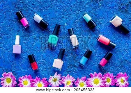 Choose nail polish for manicure. Bottles of colored polish on blue background top view.