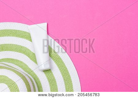Beach green straw female hat and sun protection cream on a pink background