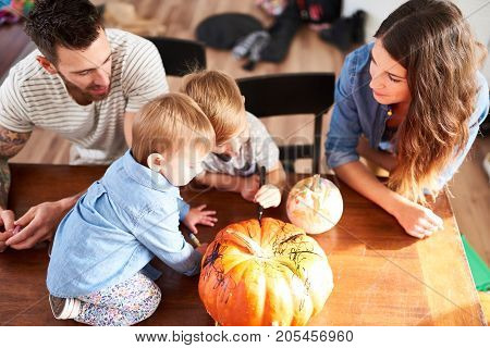 Candid scene of parents and children drawing on pumpkin with marker for Halloween