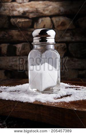 Salt Shaker and salt on wooden table.