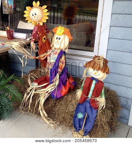 Autumn time straw children sitting on straw bale people watching. Halloween. fall time