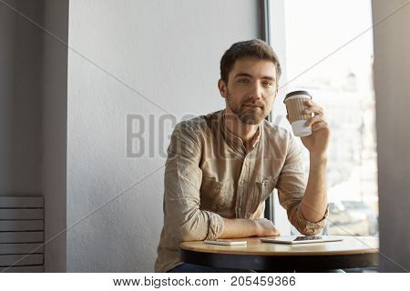 Young unshaven handsome caucasian guy in casual clothes sitting in cafeteria, drinking coffee, resting after hard day on work