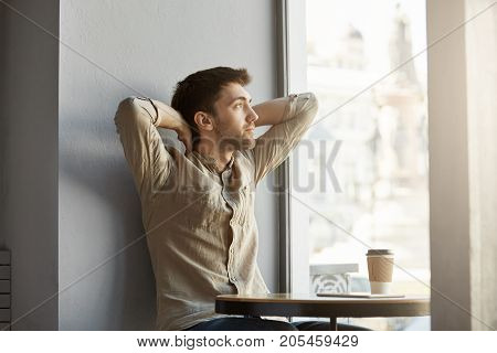 Attractive young unshaven guy sitting in cafe, looking at window with hands behind his head, exhausted after business meeting.