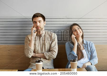 Two young people in a quarrel sitting near each other in cafeteria, looking aside, drinking coffee and talking on phones