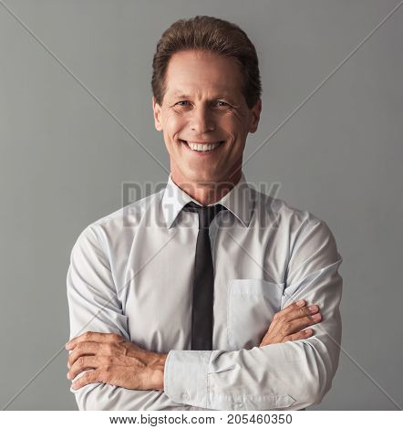 Handsome mature businessman in suit is looking at camera and smiling while standing with crossed arms on gray background