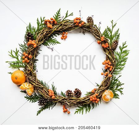 Festive wreath of grape vines with tangerines thuja branches rowanberries and cones. Christmas DIY wreath. New Year round wreath on white background. Flat lay top view