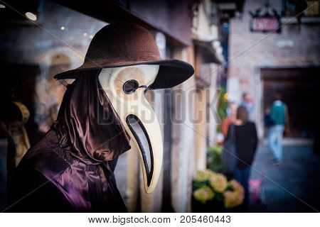 Traditional venetian mannequin in Plague doctor costume, mask and hat near shop window in the street of Venice, Italy. Toned image